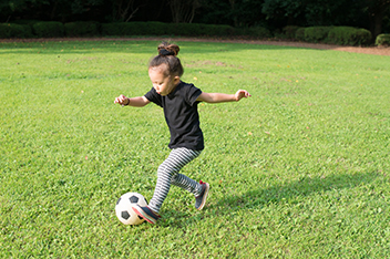 Young Girl Playing with Soccer Ball in Field