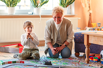 woman and boy playing with trains in home