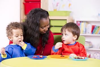teacher with two toddlers snack