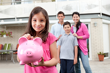 girl holding piggy bank with family
