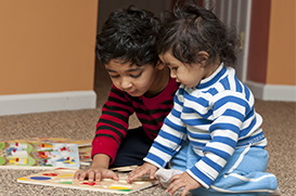 Boy and girl playing with puzzle on floor